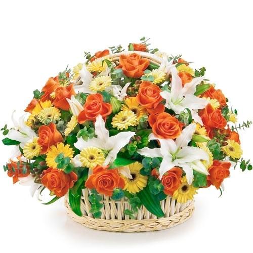 kompozycja wesoły koszyk, pomarańczowe róże, gerbery, białe lilie, zieleń dekoracyjna, kompozycja kwiatów w wiklinowym koszu z pałąkiem