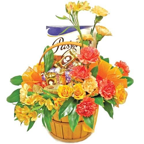 kompozyja złote lato, pomarańczowa kompozycja kwiatów, alstromeria, goździki, róże, zieleń dekoracyjna, kompozycja w drewnianym koszyku z pałąkiem z bombonierką i czekoladkami