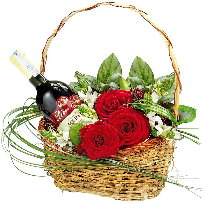 A basket with wine, red roses with decoration in the basket, red wine with flowers in the basket
