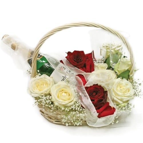 Composition of flowers in a basket with sparkling wine and two glasses, a wedding bouquet, white and red roses, gypsophila