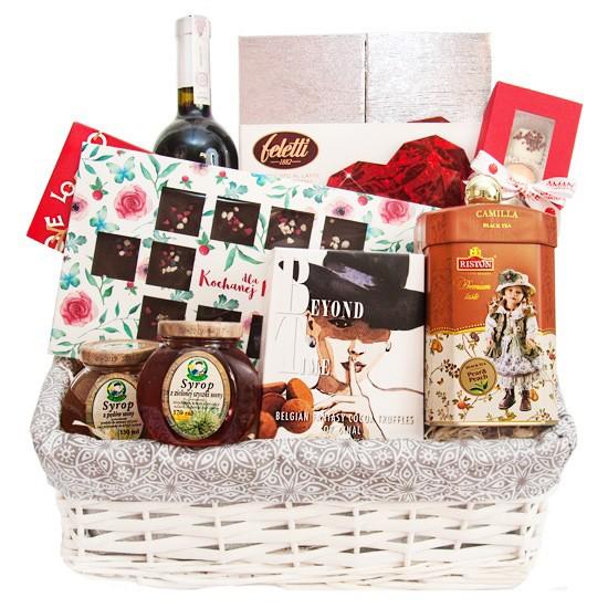 Koszyk ze słodyczami dla mamy, wino i praliny w jasnym wiklinowym koszyku