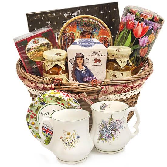 Koszyk wymalowany, wiklinowy koszyk z herbata ciastkami i śliwkami w czekoladzie
