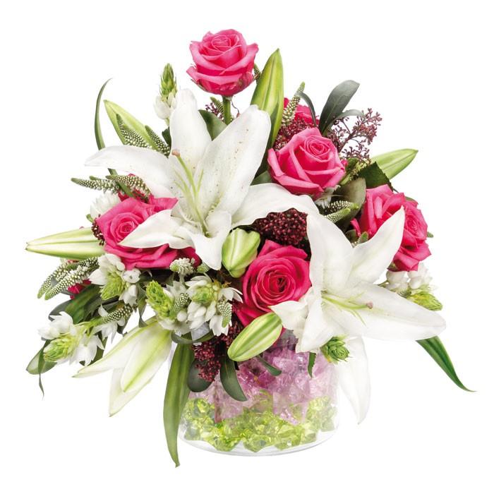 kompozycja kryształowy kielich, bukiet w szklanej wazie, różowe róże, białe lilie, zieleń dekoracyjna, zielone i fioletowe kryształki w szklanym naczyniu