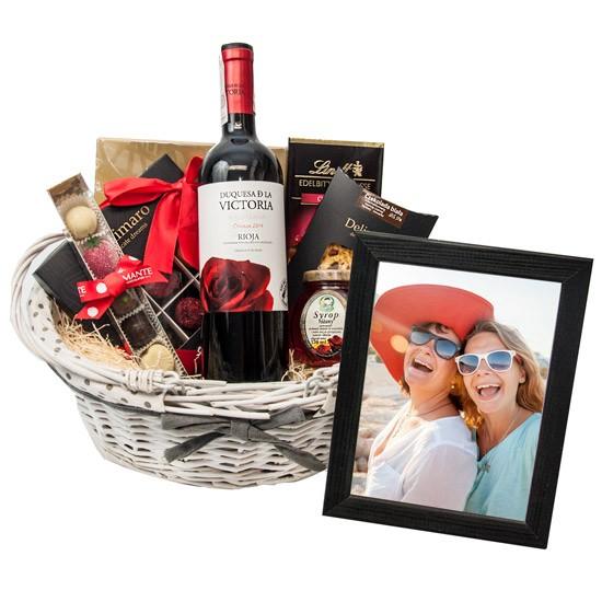 Prezent na Dzień Babci i Dziadka ze zdjęciem, koszyk ze słodyczami i winem, ramka ze zdjęciem